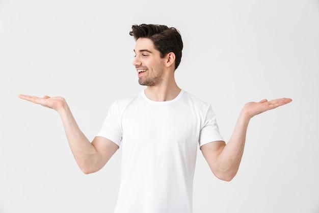 Portret wesołego młodego mężczyzny noszącego zwykłą odzież na białym tle nad białym, przedstawiającego przestrzeń kopii