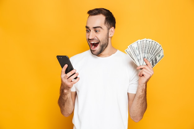 Portret wesołego młodego mężczyzny stojącego na białym tle nad żółtą ścianą, pokazującego banknoty pieniędzy, używającego telefonu komórkowego
