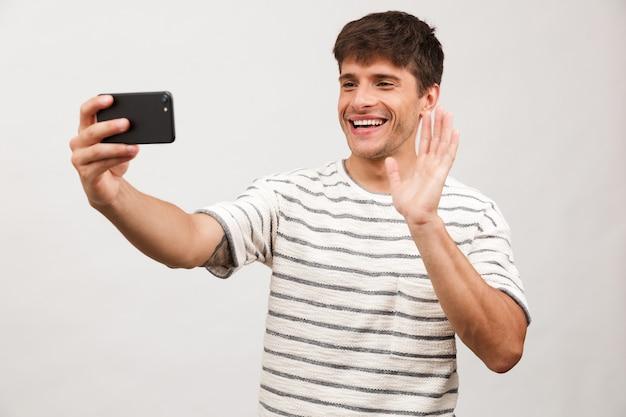 Portret wesołego młodego mężczyzny stojącego