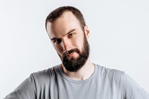 Portret wesołego młodzieńca uśmiechającego się patrząc na kamerę trzymającą ręce na boki na białym tle z miejscem na reklamę makiety