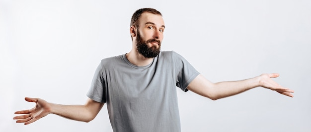Portret wesołego młodzieńca, uśmiechającego się, patrząc na przód, rozkładającego ręce na boki z ignorancji na białej ścianie