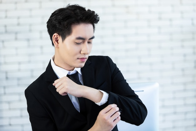 Portret wesołego nastroju młody biznesmen azjatycki zakłada spinki do mankietów, nosi garnitur mężczyzny w czarnej kurtce i białej koszuli w białej ścianie biurowej