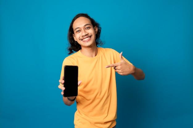 Portret wesołego pozytywnego, atrakcyjnego faceta z długimi włosami z żółtą koszulką mającą smartfona z