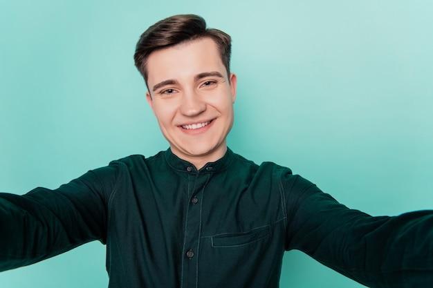 Portret wesołego pozytywnego człowieka bierze selfie ząb promienny uśmiech na turkusowym tle