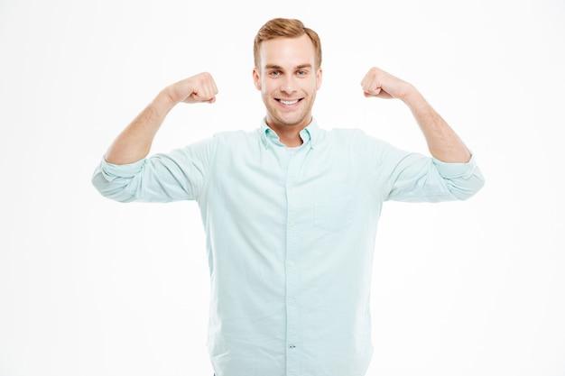 Portret wesołego przypadkowego mężczyzny pokazującego jego bicepsy na białym tle na białej ścianie