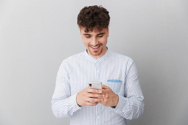 Portret wesołego przystojnego mężczyzny ubranego w koszulę uśmiechającego się podczas trzymania i używania smartfona izolowanego nad szarą ścianą