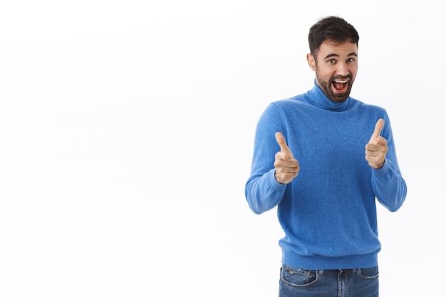 Portret wesołego, szczęśliwego brodatego mężczyzny wskazującego, gratulującego wielkiego osiągnięcia, uśmiechającego się radośnie, wybierającego lub rekrutującego osobę do zespołu lub firmy, biała ściana