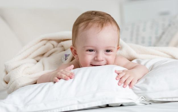 Portret wesołego uśmiechniętego chłopca relaksującego się na dużej białej poduszce na łóżku
