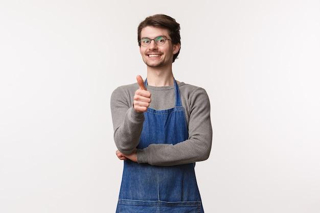 Portret wesołego, zadowolonego młodego człowieka w fartuchu, pokazujący kciuk i uśmiechnięty, gwarantuje, że spodoba ci się kawa w jego sklepie, zatwierdzisz świetne miejsce na spędzenie czasu i delektuje się deserami