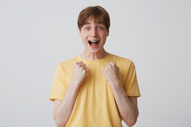 Portret wesołego zaskoczonego młodzieńca z szelkami na zębach i otwartymi ustami nosi żółtą koszulkę, jest podekscytowany i krzyczy na białym tle nad białą ścianą