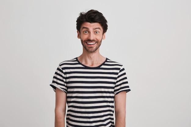 Portret wesołego, zdumionego młodzieńca z włosiem nosi koszulkę w paski, czuje się podekscytowany, stoi i wygląda na szczęśliwego na białym tle nad białą ścianą