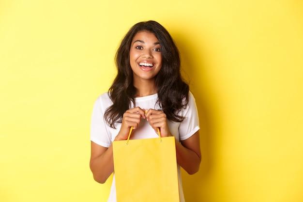 Portret wesołej afrykańskiej dziewczyny na zakupy otwierającej torbę z prezentem i uśmiechniętej szczęśliwej stojącej...