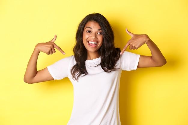 Portret wesołej afrykańskiej dziewczyny w białej koszulce wskazującej palcami twoje logo na środku st...
