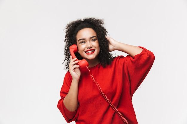 Portret wesołej afrykańskiej kobiety stojącej na białym tle nad białym tłem, rozmawiającej przez telefon stacjonarny