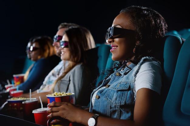 Portret wesołej afrykańskiej kobiety uśmiechającej się radośnie podczas oglądania filmu w miejscowym kinie