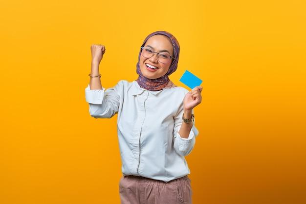 Portret wesołej azjatki świętującej szczęście i trzymającej pustą kartę na żółtym tle