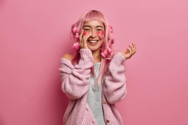 Portret wesołej azjatki używa hydrożelowych plastrów o działaniu przeciwzmarszczkowym, nosi lokówki na różowych włosach, szczerze się uśmiecha, nosi swobodny sweter