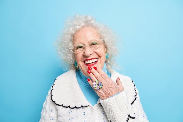 Portret wesołej babci trzyma rękę na brodzie wyraża pozytywne emocje ma zadbaną zdrową skórę i cerę nosi biały sweter słyszy coś dobrego