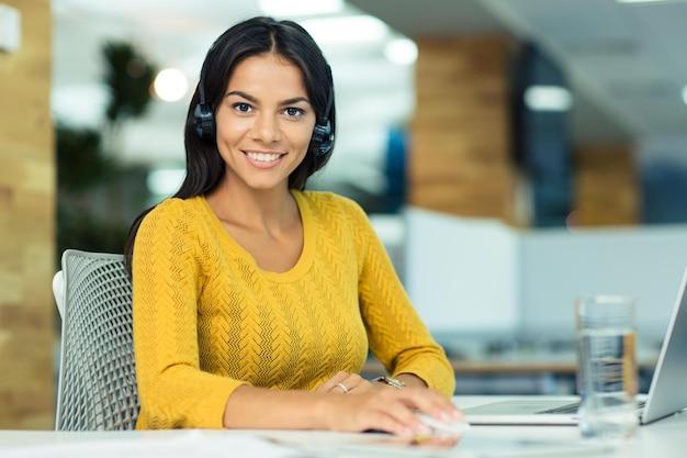 Portret wesołej bizneswoman w słuchawkach siedzącej w swoim miejscu pracy w biurze