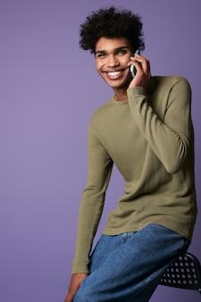 Portret wesołej brunetki rozmawiającej przez telefon komórkowy w casualowej koszulce