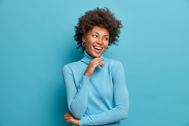 Portret wesołej ciemnoskórej kobiety z kręconymi włosami, delikatnie dotyka brody, radośnie się śmieje, cieszy się wolnym dniem, czuje się szczęśliwa i entuzjastyczna, słyszy coś pozytywnego, nosi swobodny niebieski golf