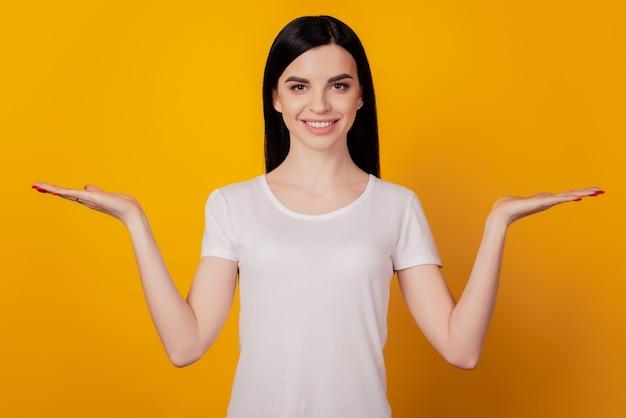 Portret wesołej damy trzyma reklamy promo uśmiech plusy minusy propozycja na białym tle na żółtym tle