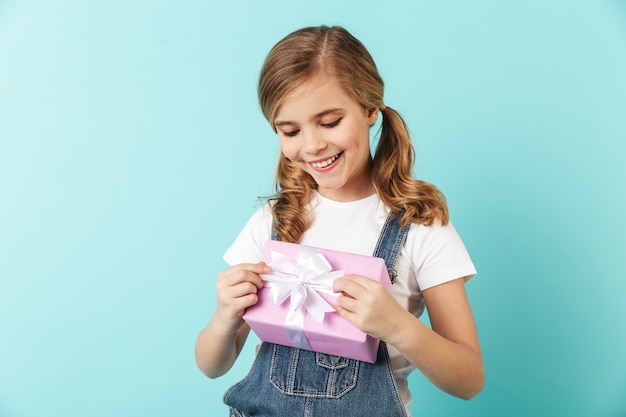 Portret wesołej dziewczynki odizolowanej na niebieskiej ścianie, pokazującej pudełko na prezent