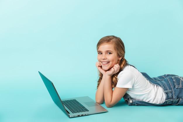 Portret wesołej dziewczynki odizolowanej nad niebieską ścianą, studiującej z laptopem