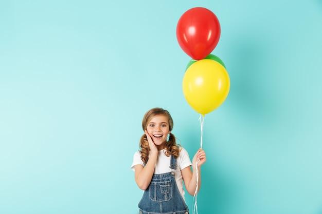 Portret wesołej dziewczynki odizolowanej nad niebieską ścianą, trzymającej pęk kolorowych balonów