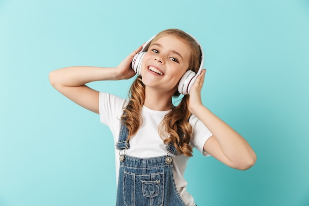 Portret wesołej dziewczynki odizolowanej nad niebieską ścianą, w słuchawkach