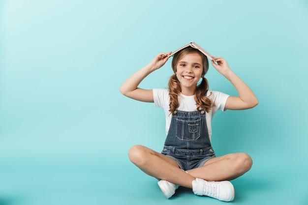 Portret wesołej dziewczynki siedzącej na białym tle nad niebieską ścianą, trzymającej książkę na głowie