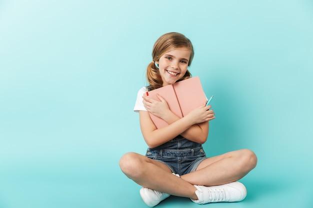 Portret wesołej dziewczynki siedzącej na białym tle nad niebieską ścianą, trzymającej książkę
