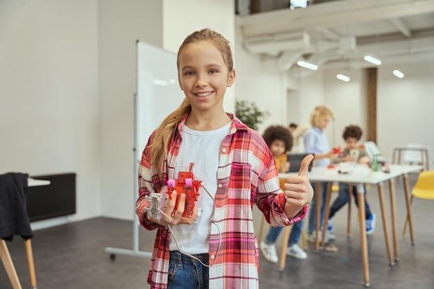 Portret wesołej dziewczynki uśmiecha się do kamery i pokazuje jej mechaniczną zabawkę, stojąc w