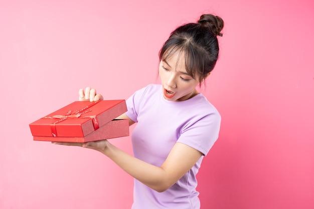 Portret wesołej dziewczyny otwierającej pudełko w dłoni, odizolowanej na różowej ścianie