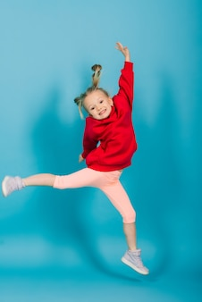 Portret wesołej dziewczyny skaczącej i tańczącej na tle studia