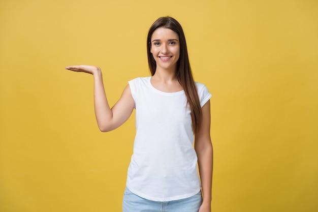 Portret wesołej dziewczyny trzymającej copyspace na dłoni na białym tle na żółtym tle