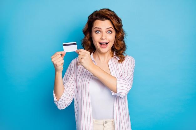 Portret wesołej dziewczyny trzymającej w ręku nową nieograniczoną plastikową kartę