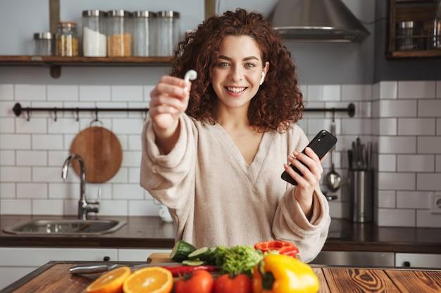 Portret wesołej europejskiej kobiety ze słuchawkami do uszu, słuchania muzyki na telefonie komórkowym podczas gotowania w kuchni w domu