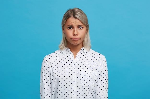 Portret wesołej, figlarnej blondynki młoda kobieta nosi koszulę w kropki, mruga, flirtuje i bawi się na tle niebieskiej ściany
