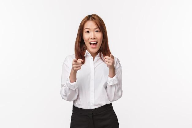 Portret wesołej i podekscytowanej przyjaznej kobiety z azji zaprasza do dołączenia do firmy, sugeruje wybranie tej kariery, wskazując palcami i uśmiechając się, wybierając osobę do zespołu, biała ściana