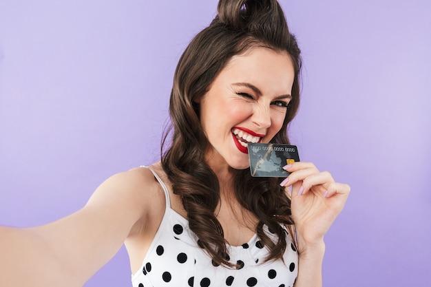 Portret wesołej kobiety pin-up w sukience vintage w kropki uśmiecha się, trzymając plastikową kartę kredytową na białym tle nad fioletową ścianą