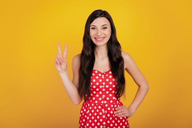 Portret wesołej kobiety pokazuje znak v biały uśmiech nosić kropkowaną czerwoną sukienkę na żółtym tle