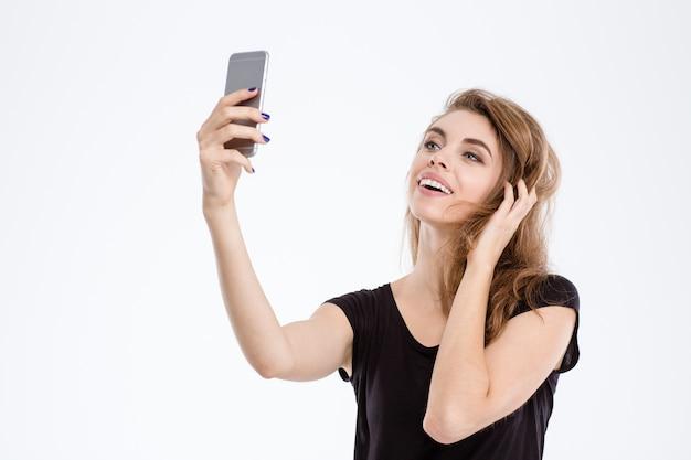 Portret wesołej kobiety robiącej zdjęcie selfie na smartfonie na białym tle