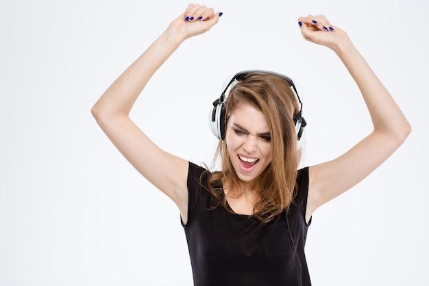 Portret wesołej kobiety słuchającej muzyki w słuchawkach i śpiewającej z podniesionymi rękami na białym tle na białym tle