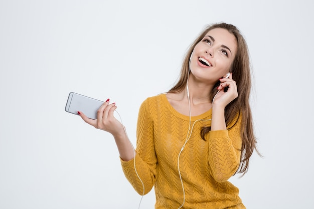 Portret wesołej kobiety słuchającej muzyki w słuchawkach na białym tle