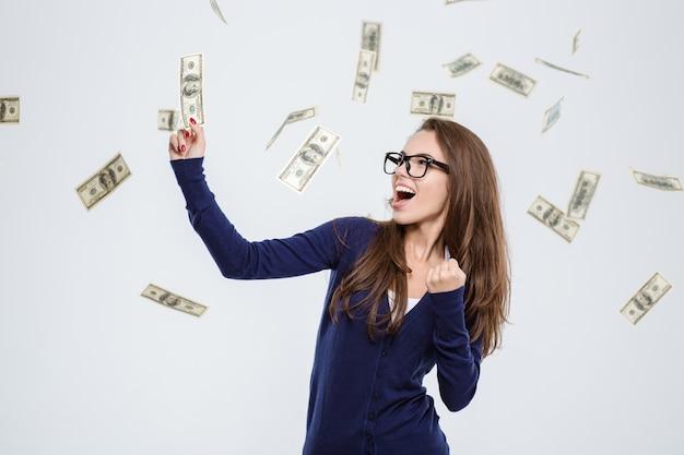 Portret wesołej kobiety stojącej pod deszczem pieniędzy na białym tle