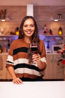 Portret wesołej kobiety trzymającej kieliszek wina