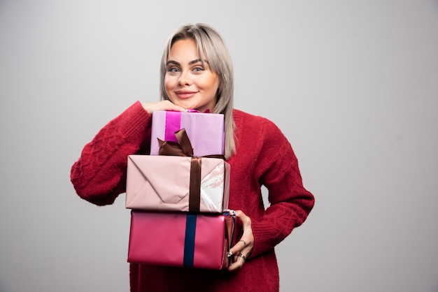 Portret wesołej kobiety trzymającej prezenty świąteczne na szarym tle.