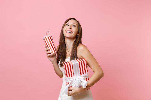 Portret wesołej kobiety w białej sukni patrzącej w górę przytrzymaj czerwone pudełko z prezentem, prezentem, plastikowym kubkiem z colą lub sodą