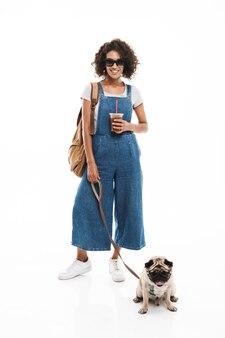 Portret wesołej kobiety w okularach przeciwsłonecznych, która pije kawę na wynos, jednocześnie przygotowując się z jej mopsem na białym tle nad białą ścianą